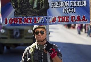 Sothy Seang, owner of the Donut Hut, marches in the Veterans Day parade in downtown Las Vegas Monday, Nov. 11, 2013. Seang fought with the Cambodian army against the Viet Cong during the Vietnam War.
