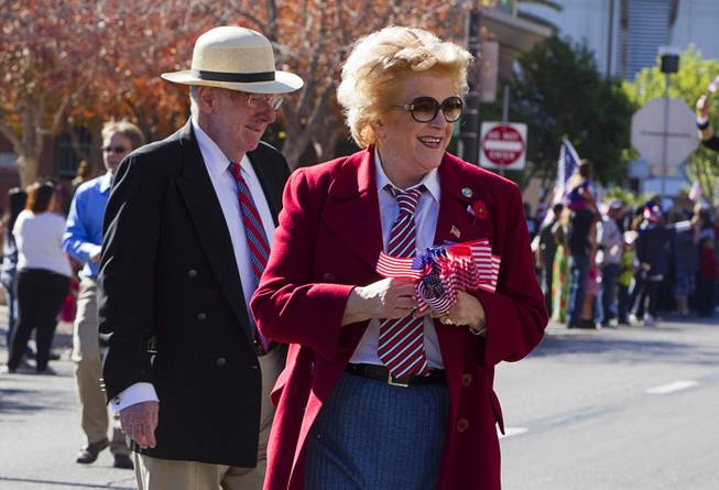 Former Mayor Oscar Goodman and his wife Mayor Carolyn Goodman hand out flags during the annual Veterans Day parade in downtown Las Vegas Monday, Nov. 11, 2013.