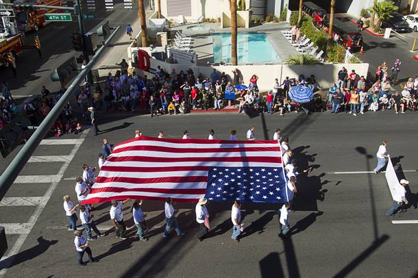 A Cox Communications entry carries an American flag during the annual Veterans Day parade in downtown Las Vegas Monday, Nov. 11, 2013.