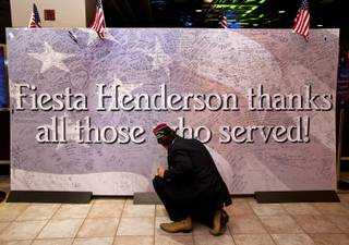 Greg Bashaw, as commander of the Henderson VFW Post 3848, joins others at the Fiesta Casino to sign a banner for Veteran's Day and enjoy a free buffet for those who served in the military on Monday, Nov. 11, 2013.