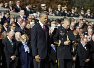 President Barack Obama and Maj. Gen. Jeffrey S. Buchanan of the U.S. Army Military District of Washington, left, lower their heads after the president placed a wreath at the Tomb of the Unknowns at Arlington National Cemetery in Arlington, Va., Monday, Nov. 11, 2013, during a Veterans Day ceremony. Vice President Joe Biden and his wife Jill are at left.