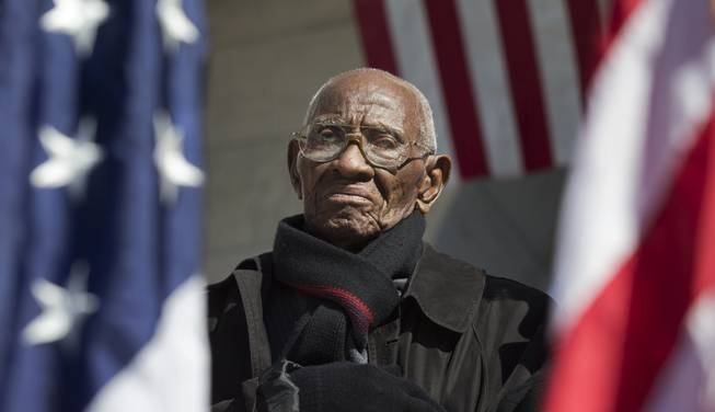 Richard Overton the oldest living WWII veteran, listens during a Veterans Day ceremony attended by President Barack Obama on Monday, Nov. 11, 2013, at Arlington National Cemetery.