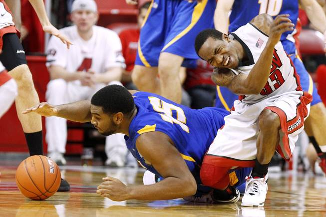 UC Santa Barbara forward Alan Williams falls on UNLV guard Deville Smith's ankle during their game Tuesday, Nov. 12, 2013 at the Thomas & Mack Center.  UC Santa Barbara won the game 86-65.