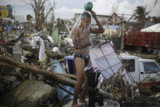 A man takes a shower amid rubble in an area badly affected by Typhoon Hayan in Tacloban, central Philippines, Wednesday, Nov. 13, 2013.