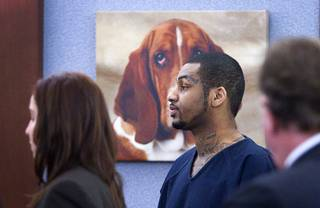 A painting of a basset hound is shown behind defendant Ammar Harris, the suspect the Feb. 21 Las Vegas Strip shooting and car crash that killed three people, as he appears in Judge Kathleen Delaney's courtroom at the Regional Justice Center Wednesday, Oct. 30, 2013. The courtroom is decorated with multiple paintings of basset hounds.