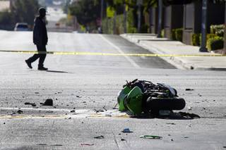 A pedestrian passes by a fatal motorcycle accident at the intersection of Flamingo and Lindell roads Thursday, Nov. 14, 2013.