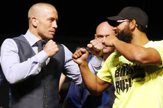 Welterweight champion Georges St. Pierre and challenger Johny Hendrics face off during a news conference Thursday, Nov. 14, 2013 in advance of UFC 167.