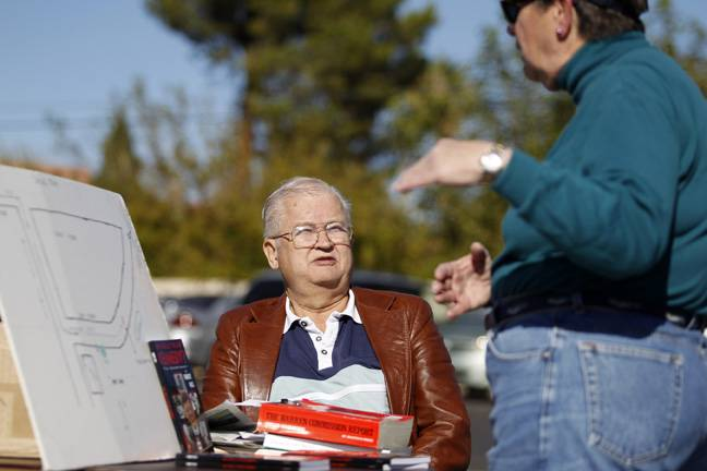 "Las Vegas resident and Kennedy assassination conspiracy theorist Bob Ries talks to a shopper while selling his book ""Who Really Killed Kennedy?"" at a church garage sale Saturday, Nov. 2, 2013."