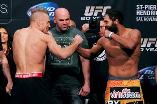 Georges St. Pierre and Johny Hendricks face off during the weigh in for UFC 167 Friday, Nov. 15, 2013.