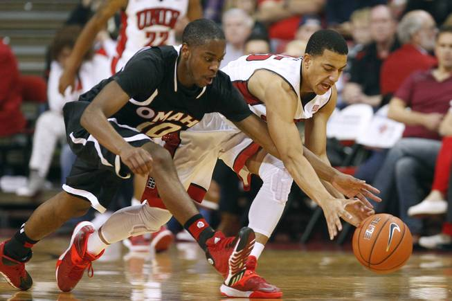 Omaha guard C.J. Carter and UNLV guard Kendall Smith chase a loose ball during their game Friday, Nov. 15, 2013 at the Thomas & Mack Center.