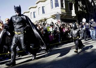 Miles Scott, dressed as Batkid, right, runs with Batman after saving a damsel in distress in San Francisco, Friday, Nov. 15, 2013.