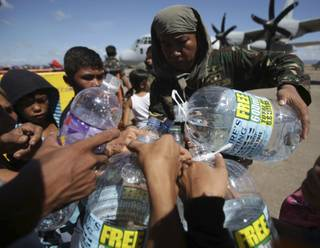 A Filipino trooper distributes water to survivors waiting for a military flight to Manila as they flee typhoon hit Tacloban city, Leyte province, central Philippines on Friday, Nov. 15, 2013.