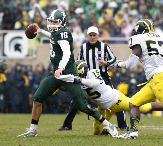 Michigan State quarterback Connor Cook (18) is stopped as he scrambles by Michigan's James Ross III (15) and Frank Clark (57) during the second quarter of an NCAA college football game, Saturday, Nov. 2, 2013, in East Lansing, Mich.