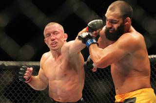 Georges St. Pierre hits Johny Hendricks with a left during their title fight at UFC 167 Saturday, Nov. 16, 2013 at the MGM Grand Garden Arena. St. Pierre won with a controversial split decision.