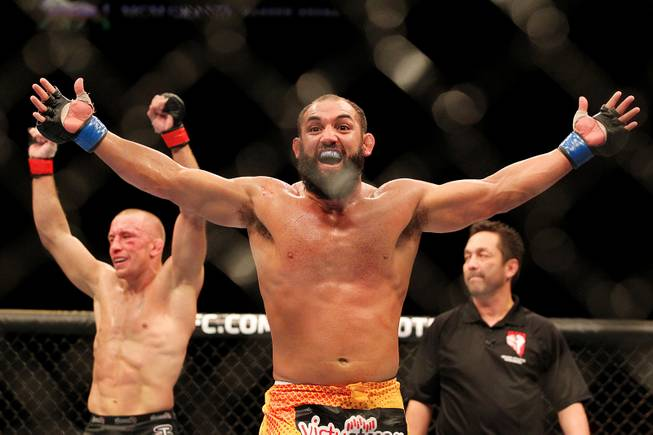 Johny Hendricks and Georges St. Pierre raise their arms after the end of their title fight at UFC 167 Saturday, Nov. 16, 2013 at the MGM Grand Garden Arena. St. Pierre retained his belt in a controversial split decision.