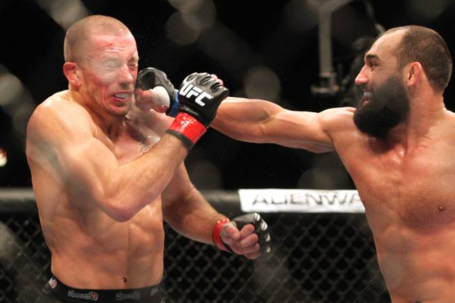 Johny Hendricks hits Georges St. Pierre with a right during their title fight at UFC 167 on Saturday, Nov. 16, 2013, at the MGM Grand Garden Arena. St. Pierre won with a controversial split decision.