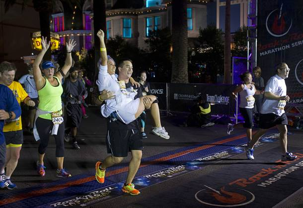 Tommy Welch, of Los Angeles, carries his wife Karla Torres-Welch over the half-marthon finish line during the 5th annual Rock 'n' Roll Las Vegas Marathon Sunday, Nov. 17, 2013. The couple renewed their wedding vows before the run.