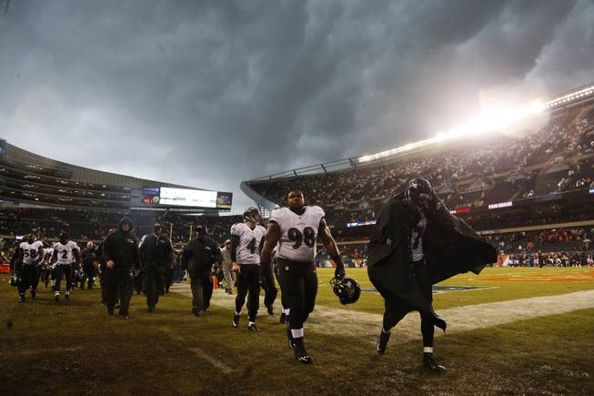Baltimore Ravens players leave the field as play was suspended for a severe thunderstorm blowing through Soldier Field during the first half of an NFL football game against the Chicago Bears, Sunday, Nov. 17, 2013, in Chicago.