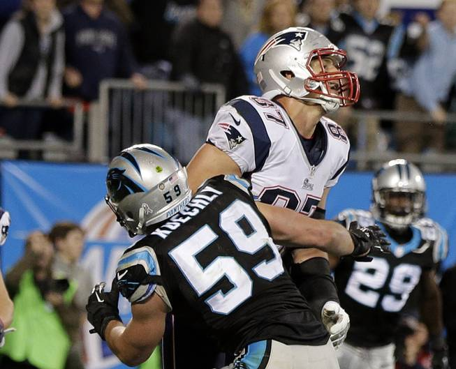 Carolina Panthers' Luke Kuechly (59) blocks New England Patriots' Rob Gronkowski (87) on the final play during the second half of an NFL football game in Charlotte, N.C., Monday, Nov. 18, 2013. The Panthers won 24-20.