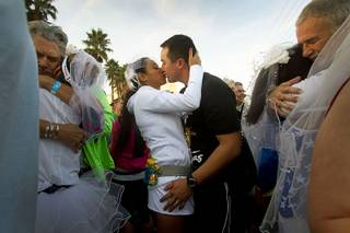 Tommy Welch and his wife Karla Torres-Welch of Los Angeles kiss during a mass ceremony for couples marrying and renewing their vows at the 5th annual Rock 'n' Roll Las Vegas Marathon Sunday, Nov. 17, 2013.