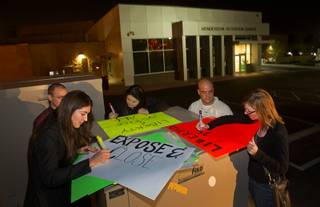 Katelyn Cantu, left, Alissa Cooley, center, and Katelyn Franklin make signs outside the Henderson Detention Center Tuesday, Nov. 19, 2013. Protesters are concerned about a UNLV law clinic report that raises questions about the conditions for immigrants at the detention center.