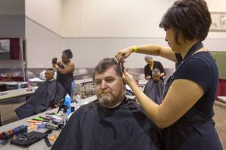 Robbie Ashley gets a haircut from stylist Rachel Dombrigues, owner of Urban Hair Company, during the Fall 2013 Southern Nevada Project Homeless Connect at Cashman Field Center Tuesday, Nov. 19, 2013. The annual event brings together a variety of social and legal services to help homeless and low-income people. STEVE MARCUS