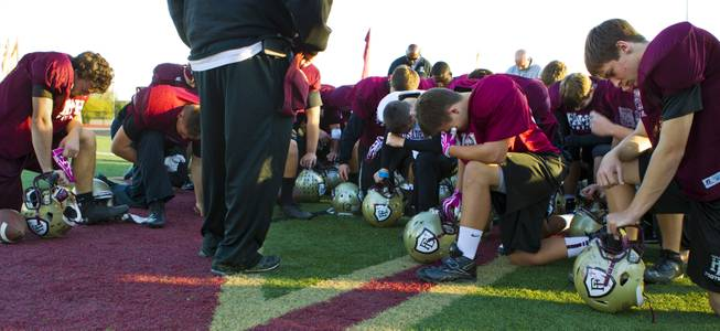 Faith Lutheran players and coaches gather for a group prayer at the start of practice on Tuesday as they gear up for their Division I-A state high school football championship game against Churchill County of Fallon.  Nov. 19, 2013.