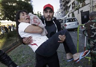 A Lebanese man carries an injured Asian domestic worker, at the scene where two explosions have struck near the Iranian Embassy killing many, in Beirut, Lebanon, Tuesday Nov. 19, 2013.