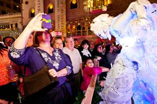 Seven-year-old Lilly Randoph, center, looks on with amazement at a snowflake entertainer on stilts as attendees snap photos during the 2013 Winter in Venice Holiday Spectacular at the Venetian Wednesday evening in Las Vegas November 20, 2013.