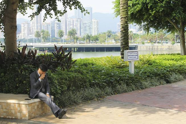 A man talks into a mobile phone with the Pearl River in the background in downtown Macau.