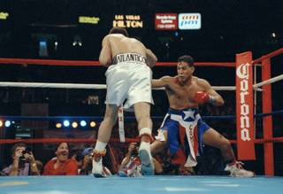 Challenger Hector Camacho gets down low in the corner while trying to avoid the relentless charge of champion Julioi Cesar Chavez during the third round of their WBC super lightweight title fight in Las Vegas, Nev., Sept 12, 1992.