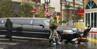 A limo driver walks away from the accident scene as a Las Vegas police officer approaches the mobile chair she struck along E. Ogden Avenue and N. Third Street. The rider was transported by ambulance with unknown injuries Thursday, Nov. 21, 2013.  L.E. Baskow