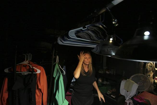 "Paula Nyland, dresser for ""Vegas! The Show,"" stages costumes in one of numerous dark corners backstage at the Saxe Theater in Las Vegas."