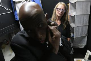 "Actor Eric Jordan Young hurries to attach a microphone as dresser Paula Nyland stands by backstage at ""Vegas! The Show,"" at the Saxe Theater in Las Vegas."