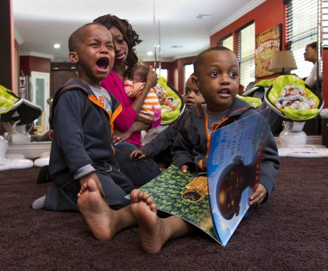 Dallas Derrico, 2, cries while his mother Evonne Derrico holds one of her quintuplets and joins her sons while they look at a book Monday, Nov. 22, 2013.