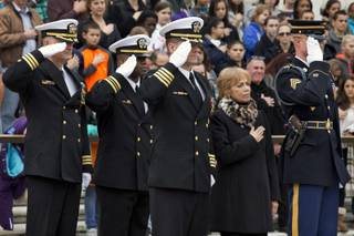 Navy SEALs salute at left, with Carmella LaSpada, a White House aide to President John F. Kennedy, and an Honor Guard soldier from the 3rd U.S. Infantry Regiment, called ''The Old Guard,'' right, at a wreath as  during the placing of a special wreath at the Tomb of the Unknowns in tribute to Kennedy, Friday, Nov. 22, 2013, at Arlington National Cemetery in Arlington, Va.,, on the 50th anniversary of Kennedy's death.
