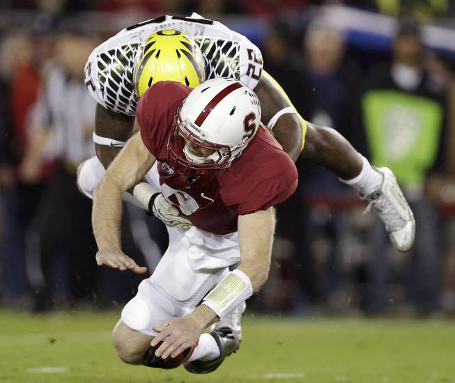 Oregon linebacker Derrick Malone (22) tackles Stanford quarterback Kevin Hogan after Hogan passed the ball during the first quarter of an NCAA college football game in Stanford, Calif., Thursday, Nov. 7, 2013.
