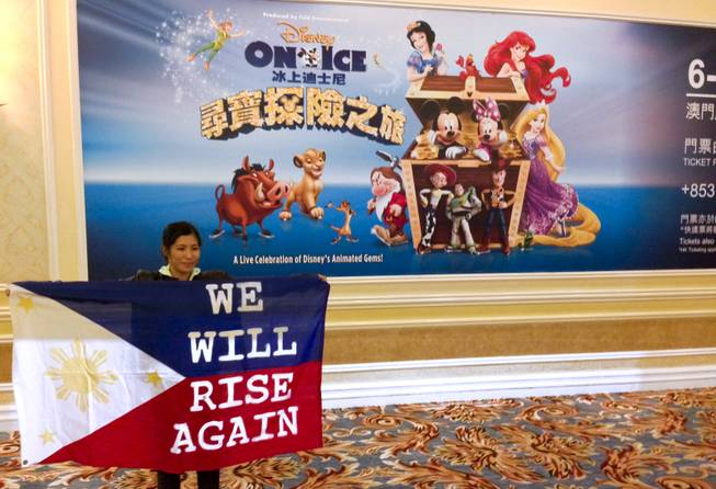 "A woman holds up a ""We Will Rise Again"" flag in front of a giant ad advertising Disney on Ice at the Venetian Macau."
