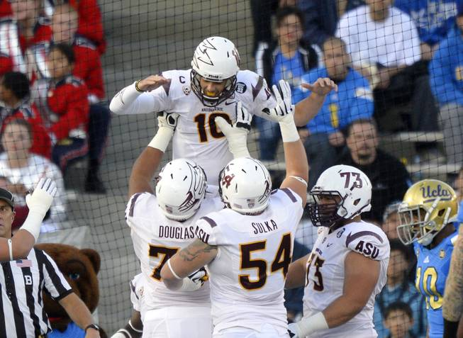 Arizona State quarterback Taylor Kelly celebrates his touchdown with offensive linesmen Jamil Douglas, Tyler Sulka and Vi Teofilo as UCLA cornerback Fabian Moreau watches during the first half of an NCAA football game Saturday, Nov. 23, 2013, in Pasadena, Calif.