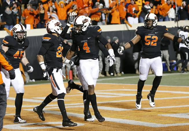 Oklahoma State's Justin Gilbert (4) celebrates with teammate Tyler Patmon (26) following Patmon's touchdown against Baylor in the fourth quarter of an NCAA college football game in Stillwater, Okla., Saturday, Nov. 23, 2013. Oklahoma State won 49-17.