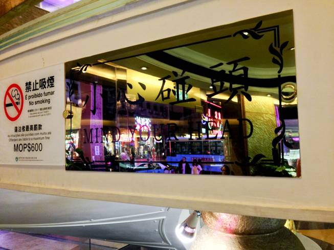 "A window with the words ""Mind Your Head"" written on it in downtown Macau."