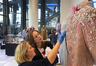Shannon Nutt, left assistant curator, and curator Dierdra Clemente look over a Liberace costume prior to the opening of