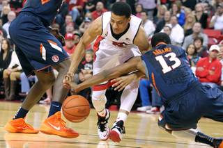 UNLV guard Kendall Smith has the ball stripped by Illinois guard Tracy Abrams during their game Tuesday, Nov. 26, 2013 at the Thomas & Mack Center. Illinois won the game 61-59.