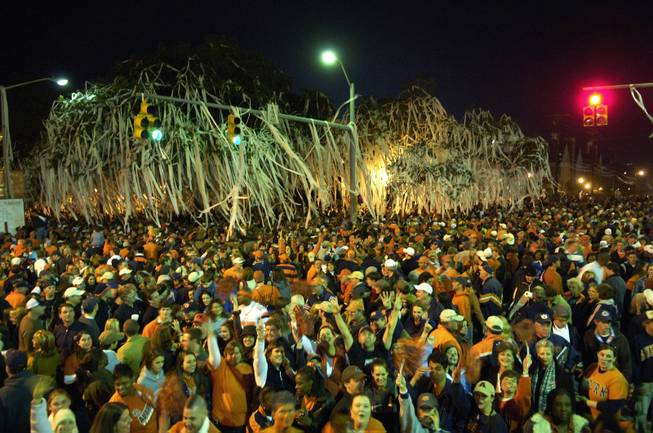 In this Nov. 19, 2005 file phot, Auburn fans celebrate by Toomer's Corners after their 28-18 win over Alabama in the Iron Bowl NCAA college football game in Auburn, Ala. The maddening, thrilling, all-consuming Alabama-Auburn rivalry polarized an entire state long before an overzealous Crimson Tide fan allegedly dealt the latest low blow by poisoning the Toomer's Corner oaks.