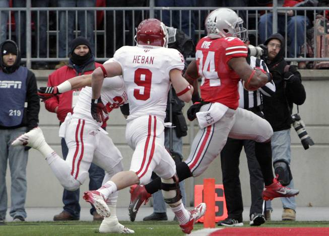 Ohio State running back Carlos Hyde, right, scores against Indiana's Mark Murphy, left, and Greg Heban during the first quarter of an NCAA college football game Saturday, Nov. 23, 2013, in Columbus, Ohio.