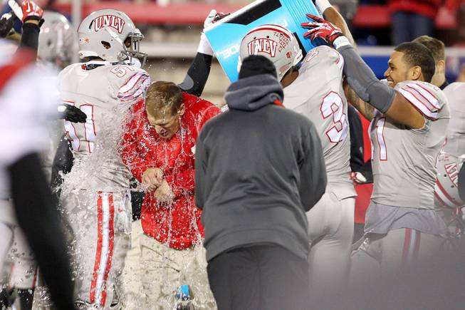 UNLV head coach Bobby Hauck gets an ice water bath as time runs out during their Mountain West Conference game against  San Diego State Saturday, Nov. 30, 2013 at Sam Boyd Stadium. UNLV won 45-19.