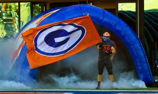 Bishop Gorman's Chris Lalli (48) waves a flag as his team readies to leave the tunnel onto the field for the regional championships on Saturday, Nov. 30, 2013.  L.E. Baskow