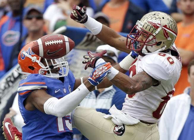 Florida defensive back Loucheiz Purifoy, left, breaks up and intercepts a pass intended for Florida State wide receiver Rashad Greene (80) during the first half of an NCAA college football game in Gainesville, Fla., Saturday, Nov. 30, 2013.