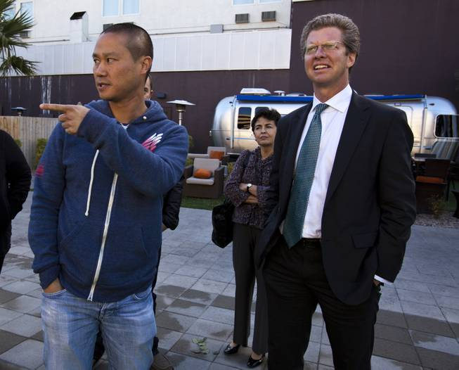 Zappos CEO Tony Hsieh, left, points out the Golden Spike during a tour of downtown Las Vegas with U.S. Department of Housing and Urban Development Secretary Shaun Donovan on Wednesday, Dec. 4, 2013.