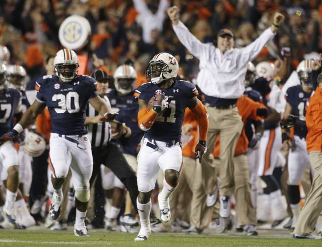 In this Nov. 30, 2013 file photo, Auburn cornerback Chris Davis (11) returns a field goal attempt 109-yards to score the winning touchdown over Alabama during the second half of an NCAA college football game in Auburn, Ala. Davis's 109-yard return of a missed field goal to beat Alabama was one of the Iron Bowl's and the season's most memorable plays.
